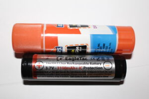 A typical 18650 battery compared in size to a typical glue stick!