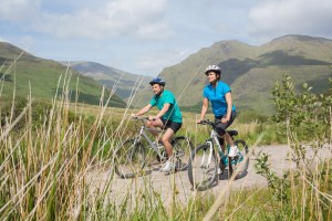 Fit attractive couple cycling together through majestic countryside